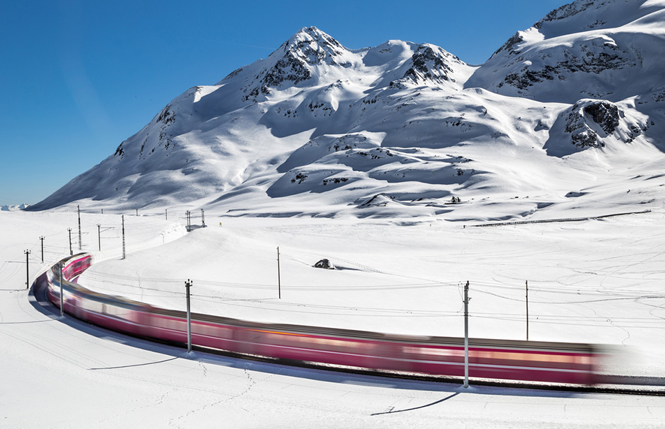 Swiss train travels through a snow-covered alpine landscape